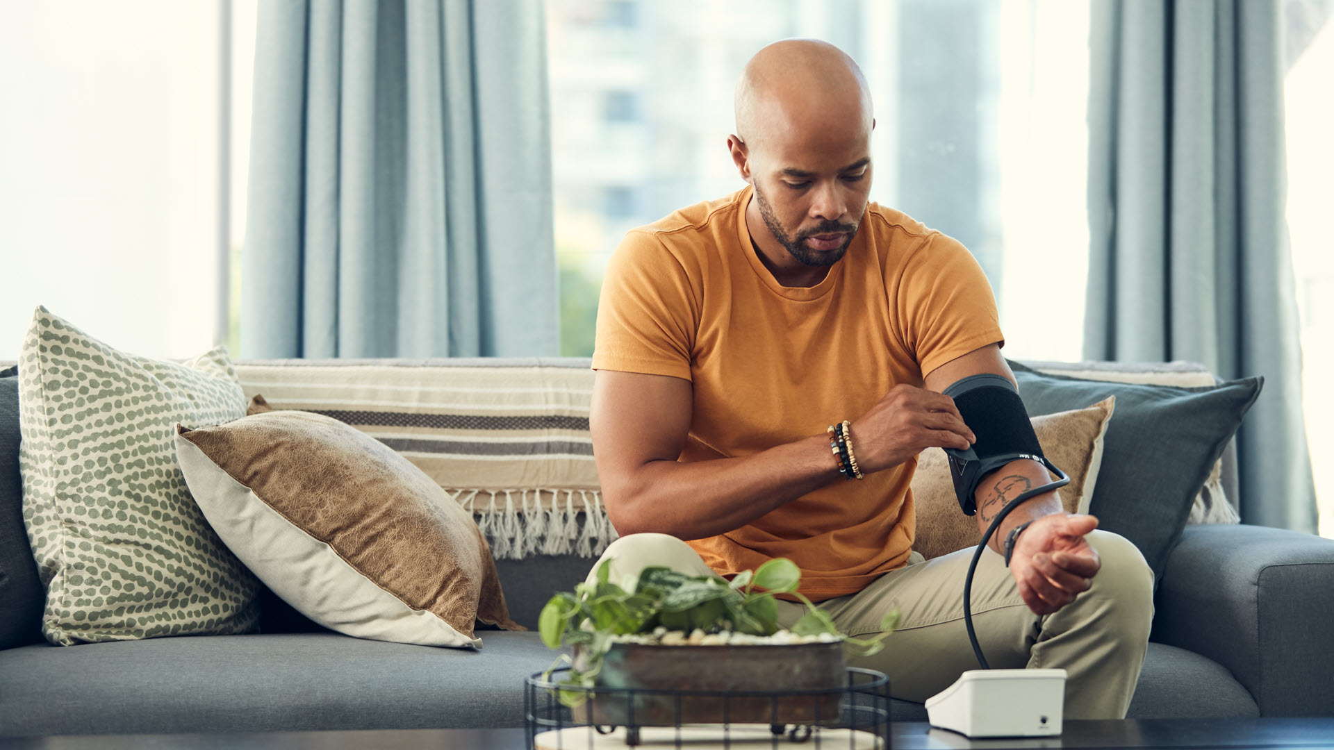 Man sitting on couch at home taking his blood pressure