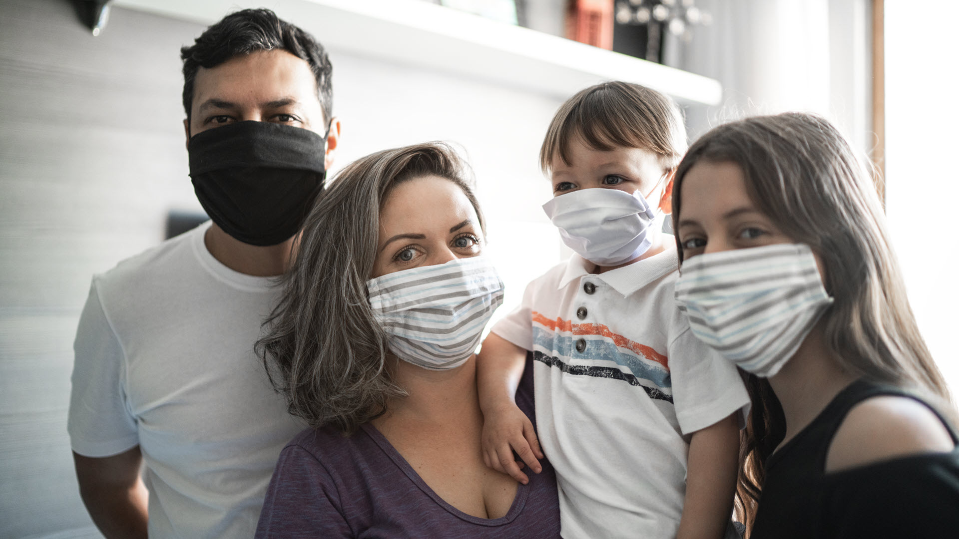 Family of four wearing masks staring attentively at the camera