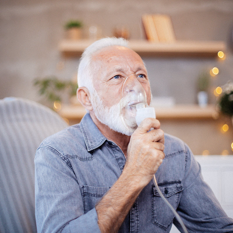 Man with shortness of breath receiving supplemental oxygen by mask