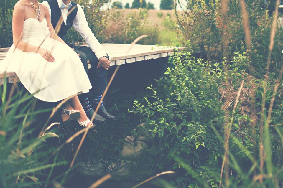 A married couple sits on a bridge.