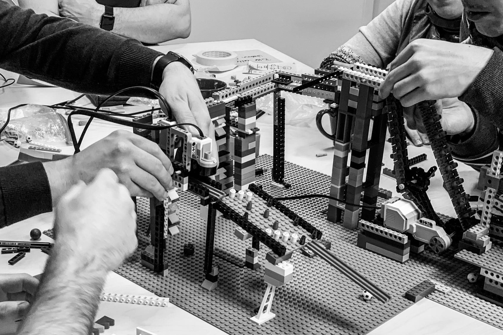 Teilnehmer:innen lösen eine Teamaufgabe mit Lego-Steinen