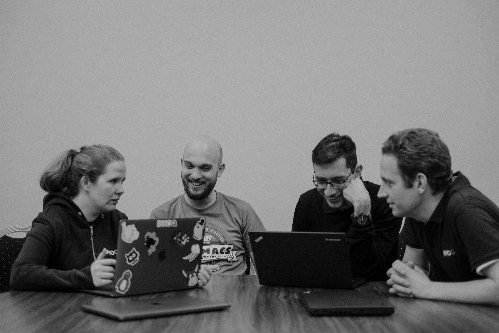 Vier Menschen, die zusammen bei der Arbeit an einem Tisch sitzen und an Notebooks arbeiten, darunter Lisa Maria Moritz und Lucas Dohmen, beide Consultants bei INNOQ und Trainer:innen des JavaScript Trainings.