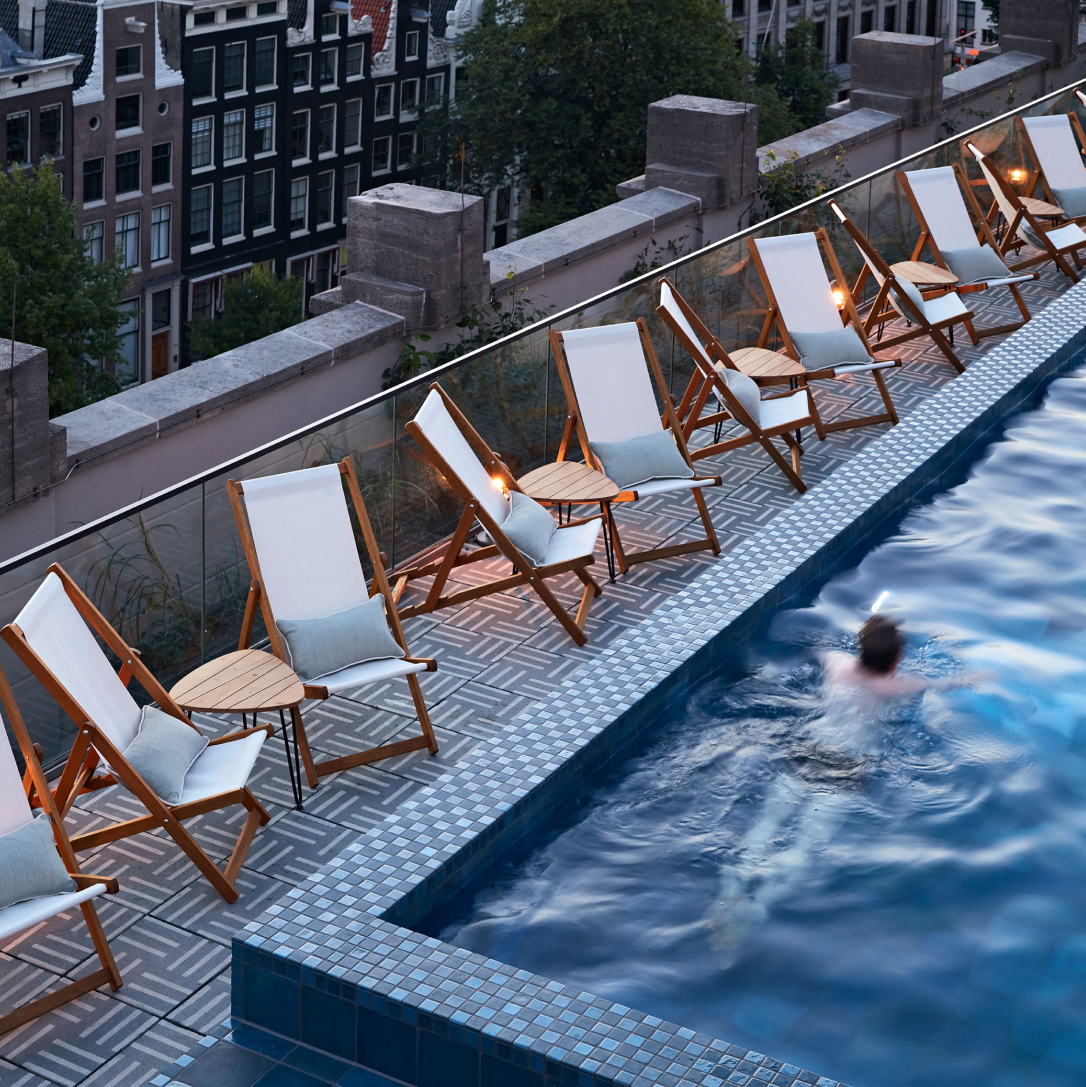 A person swimming in a rooftop pool surrounded by deckchairs with a city street below.