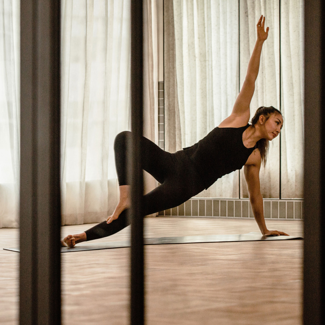 A woman stretches with her arm in the air during a yoga class in a gym studio.