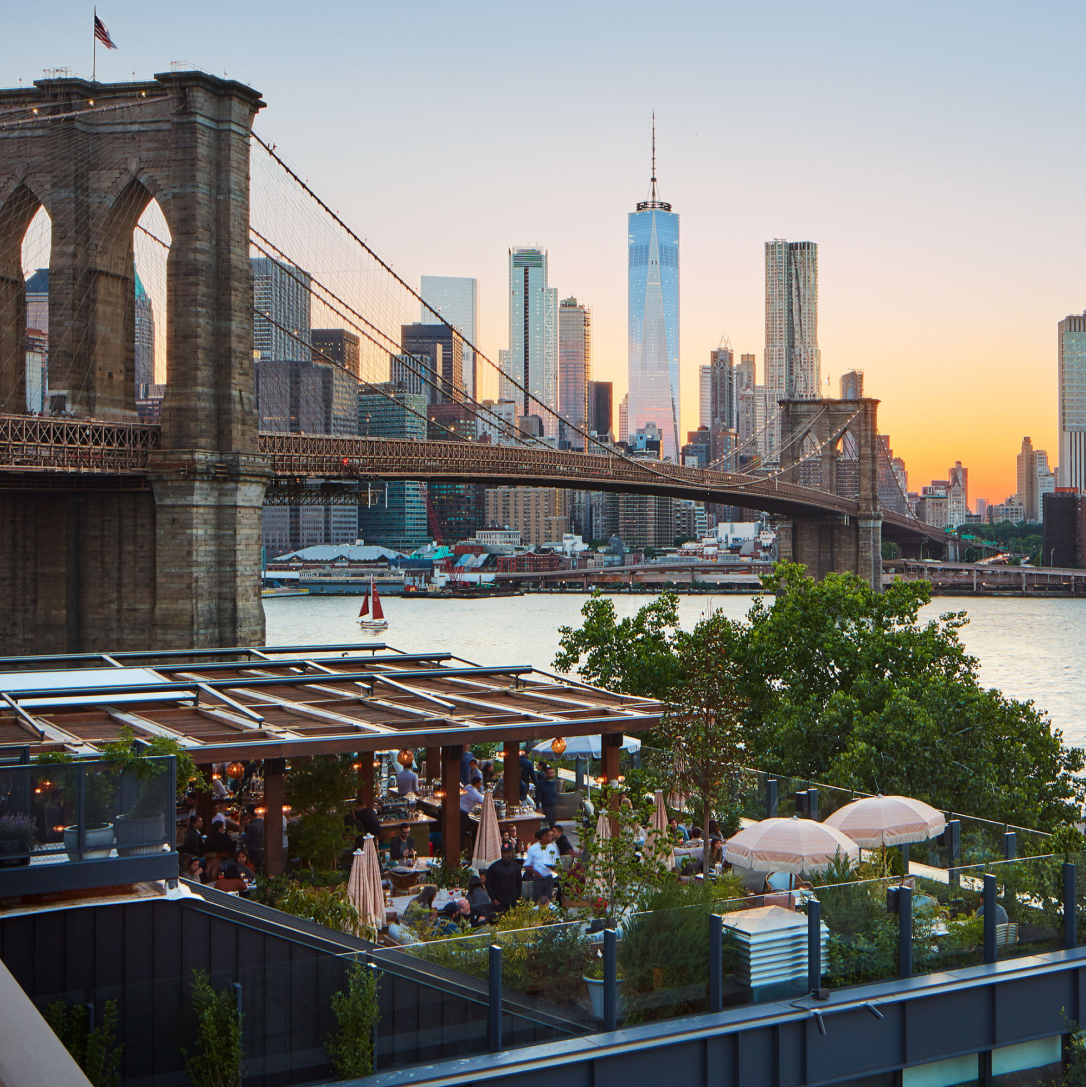 A terrace overlooking a large bridge and river with a cityscape full of tall buildings in the background at sunset.