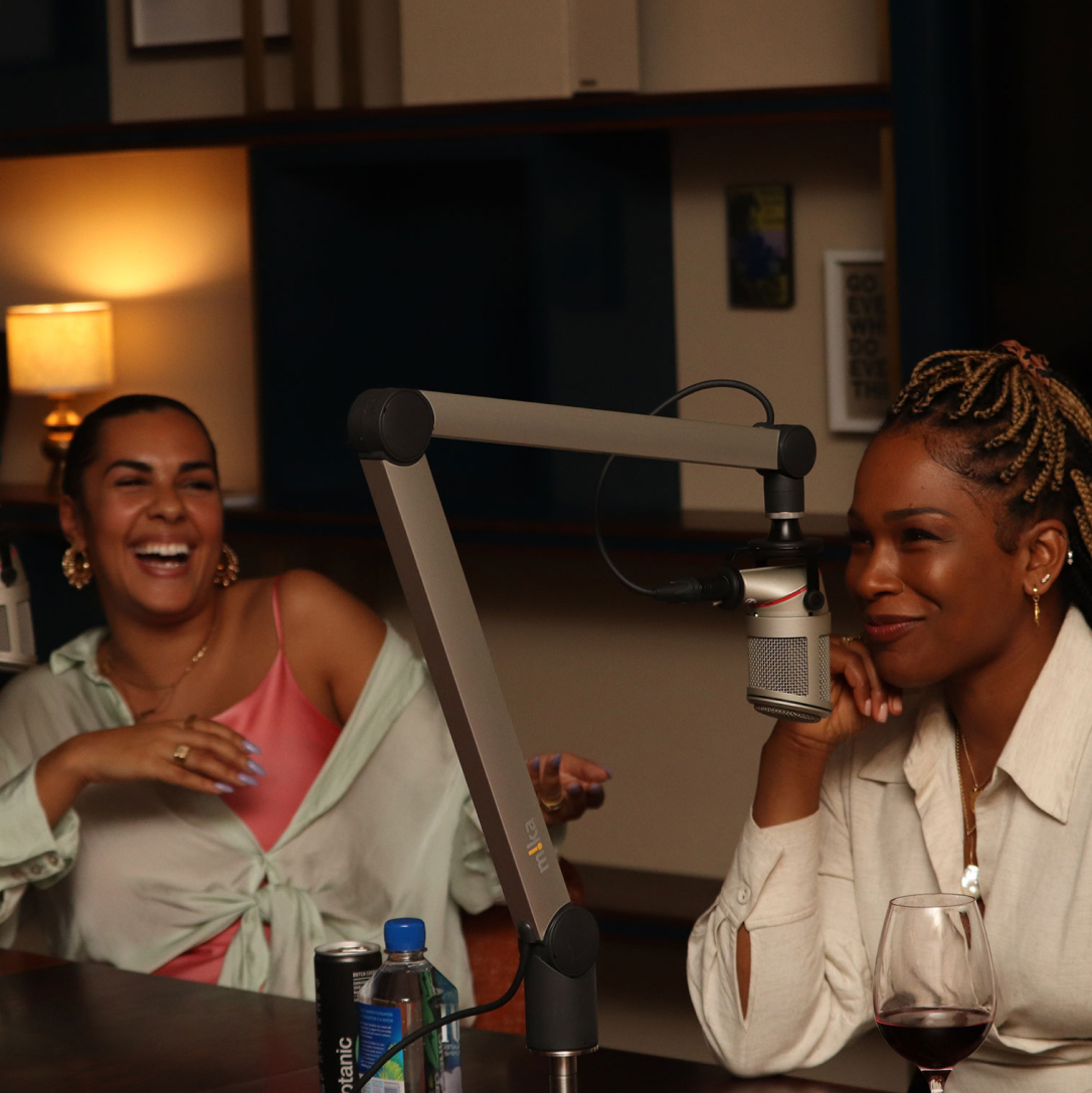 Two women using recording equipment in an office with one laughing at the other.