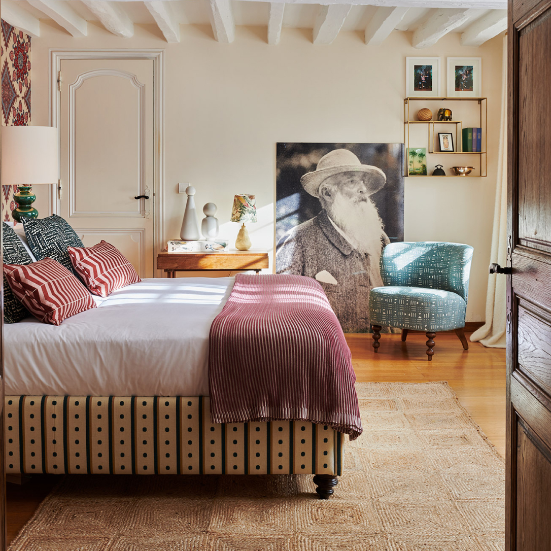 A bedroom with many soft furnishings and other decorations.