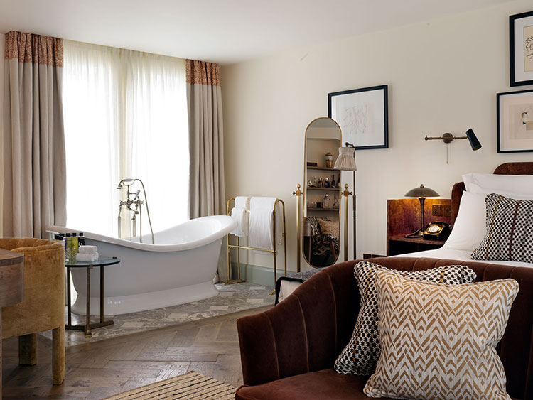 A large bedroom with a roll top bath next to the bed.