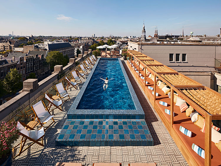 A person swimming in a rooftop pool on a sunny day.