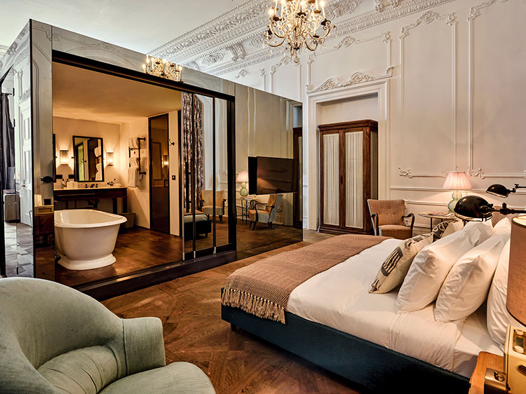 A high-ceilinged, large, ornate bedroom with a large mirrored glass box in it containing a bathroom.