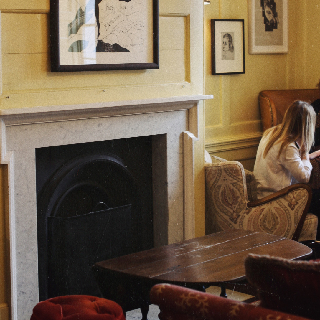 A fireplace in a yellow room with a person sat next to it.