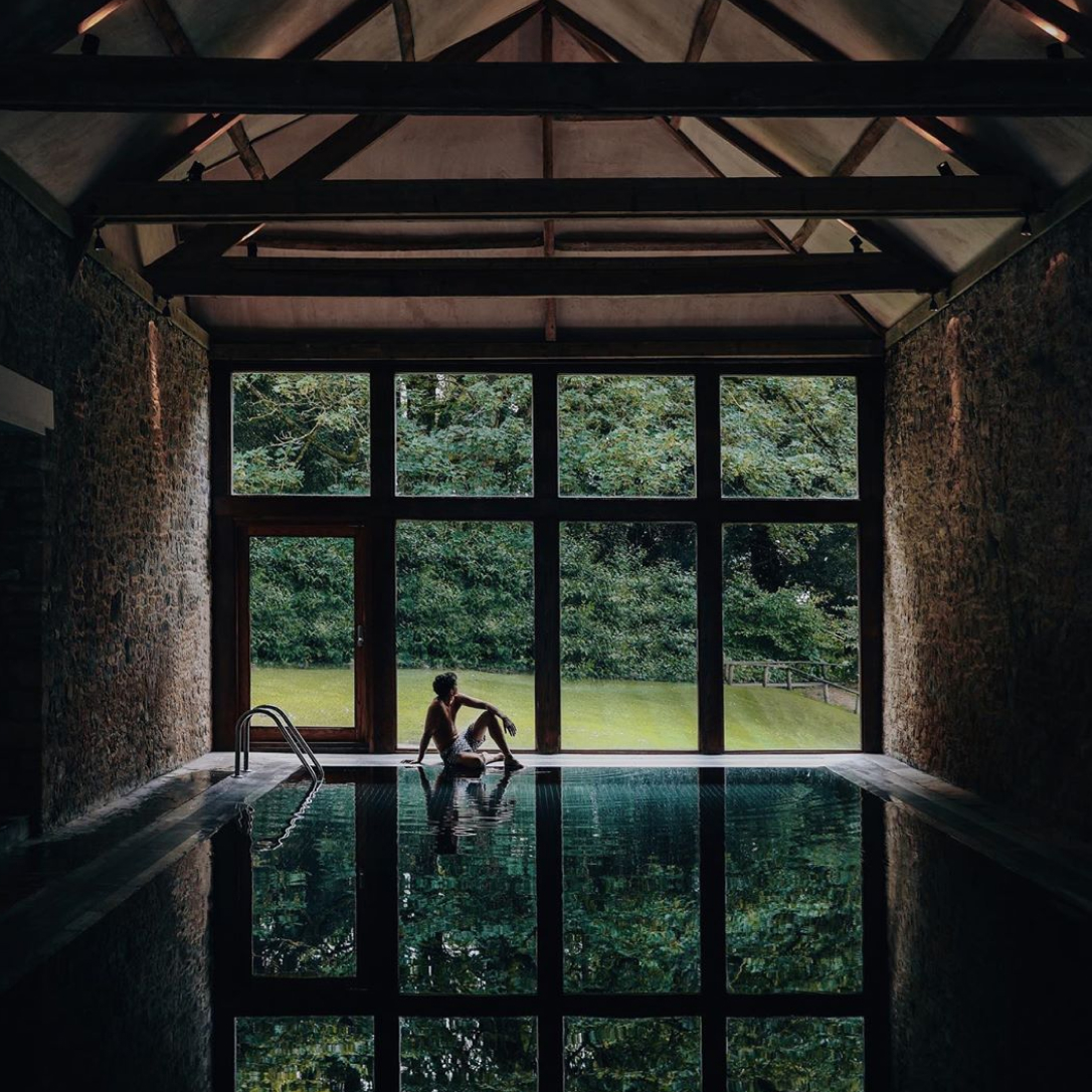 A man sits at the end of an indoor pool.