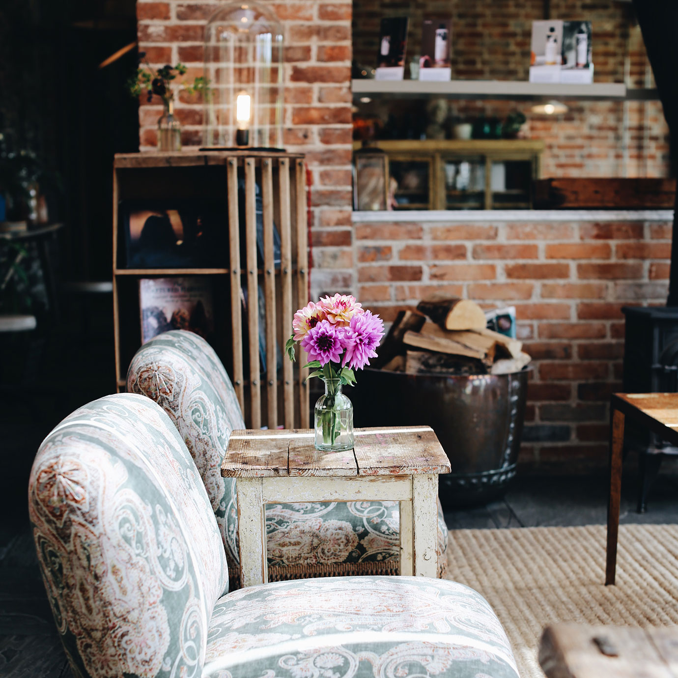 Two chairs and a vase of flowers on a table.