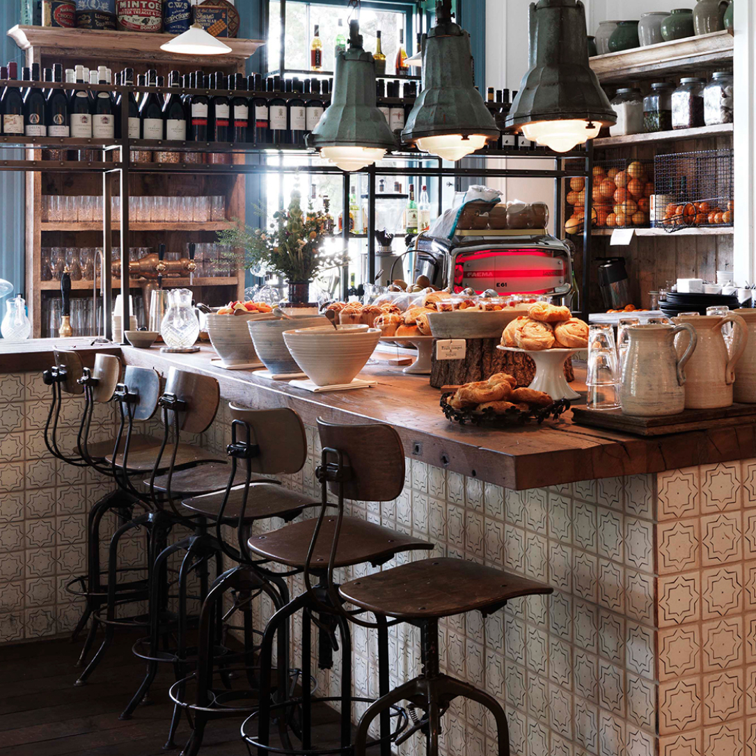 A breakfast bar with high chairs and food on the surface.