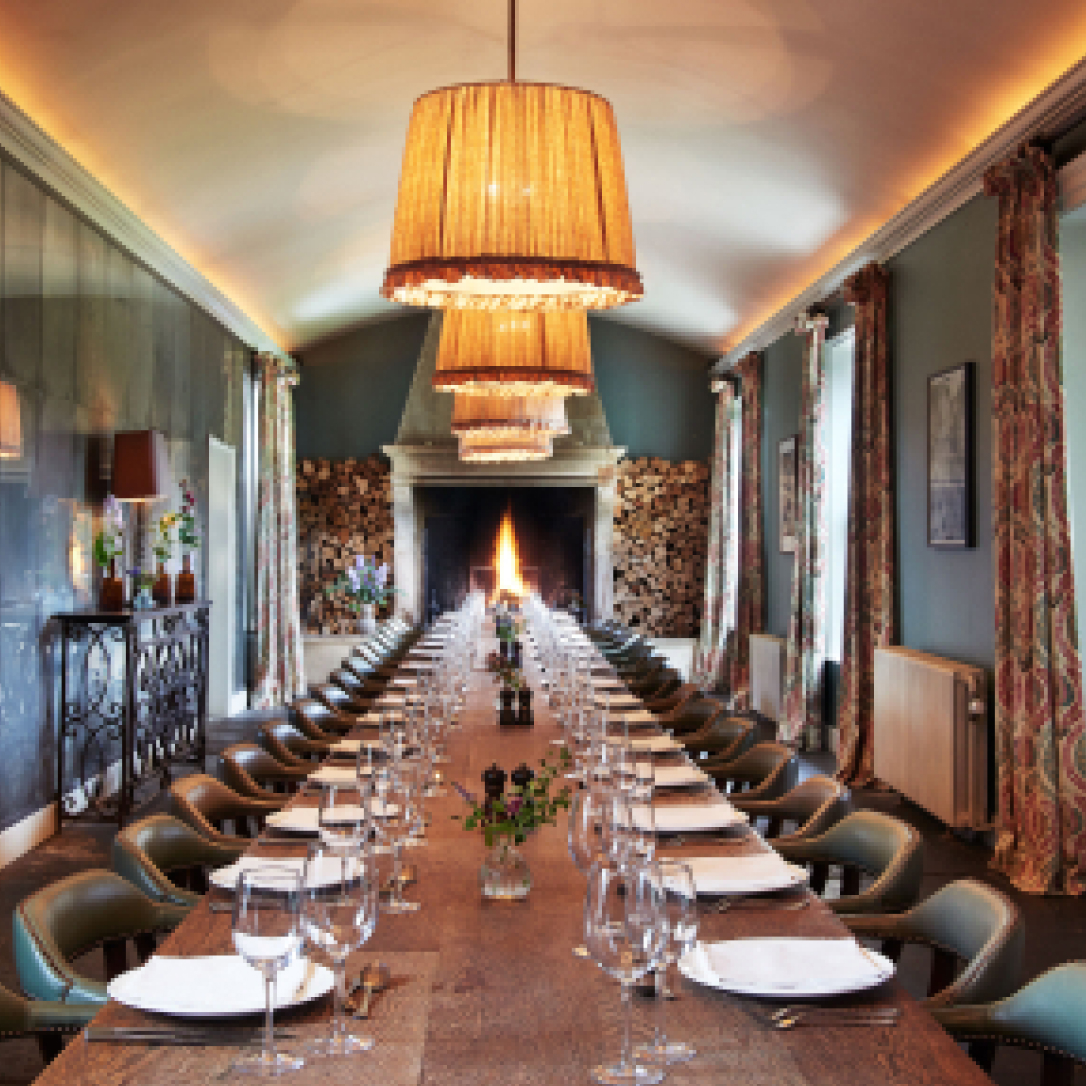 A large dining table laid for a formal dinner with a burning log fire at the far end.