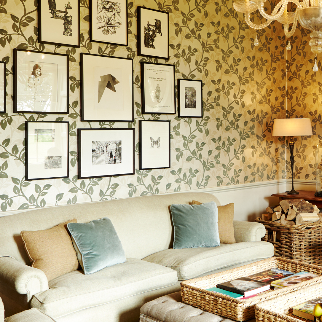 A small lounge area with a sofa and artworks on the walls.