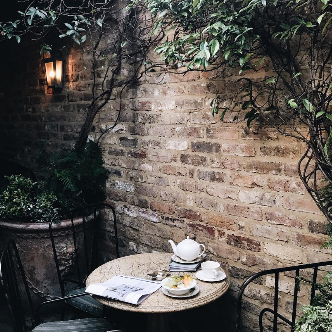 A outdoor terrace area with brick walls, plants and a table and chairs with a tea set laid on it.