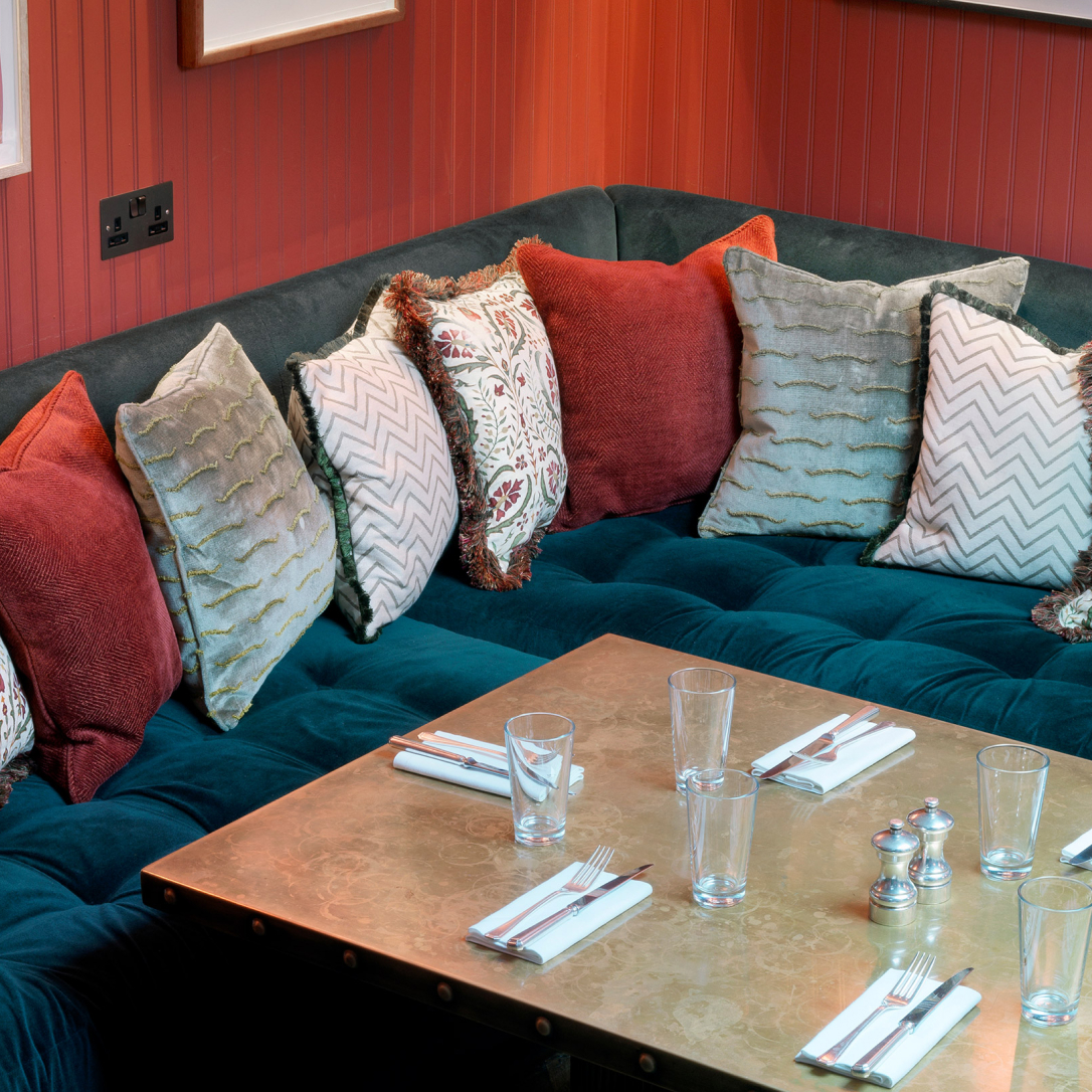 A cosy space with a table, seating and cushions.