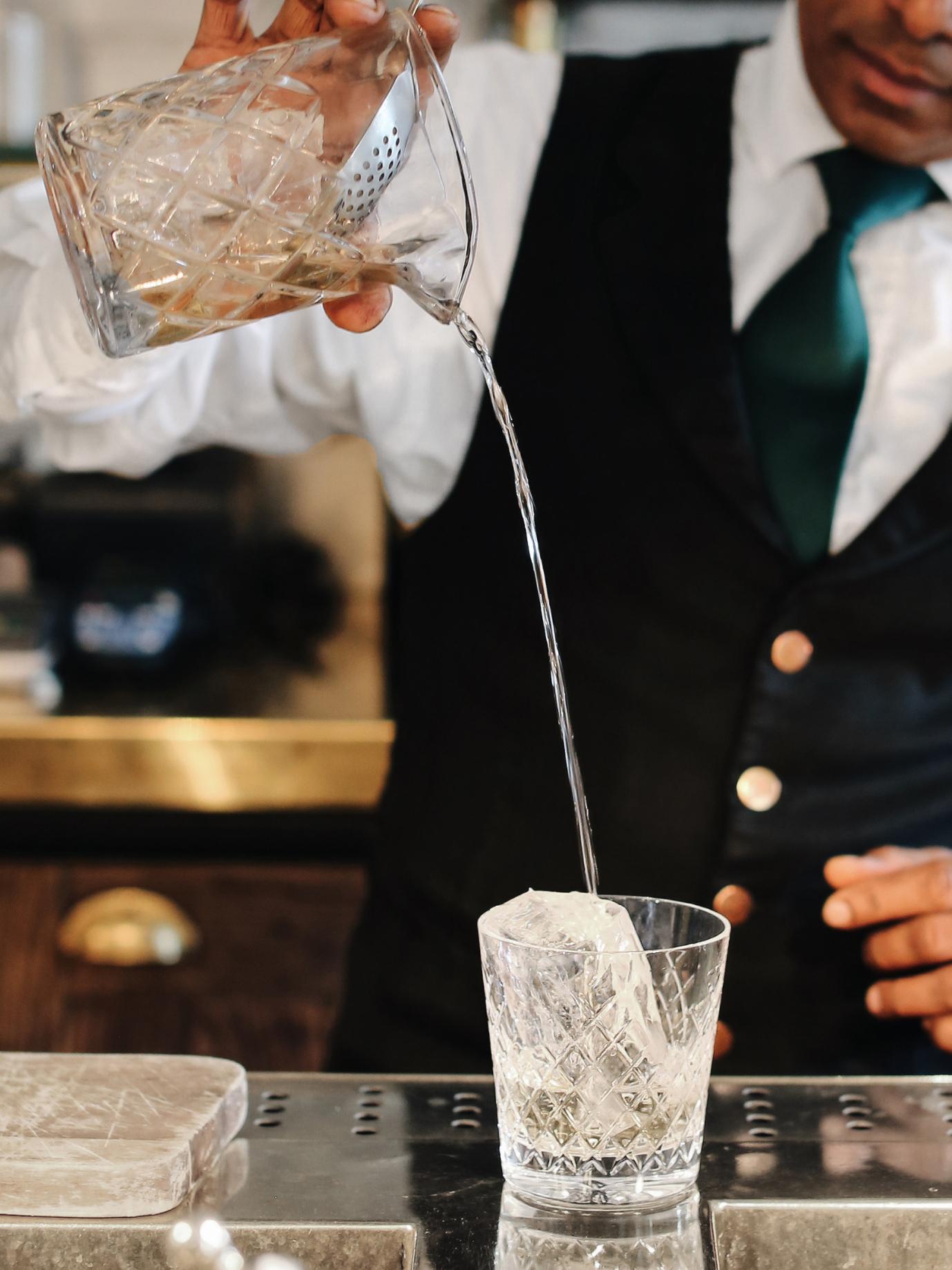 A barman pours liquid into a glass.