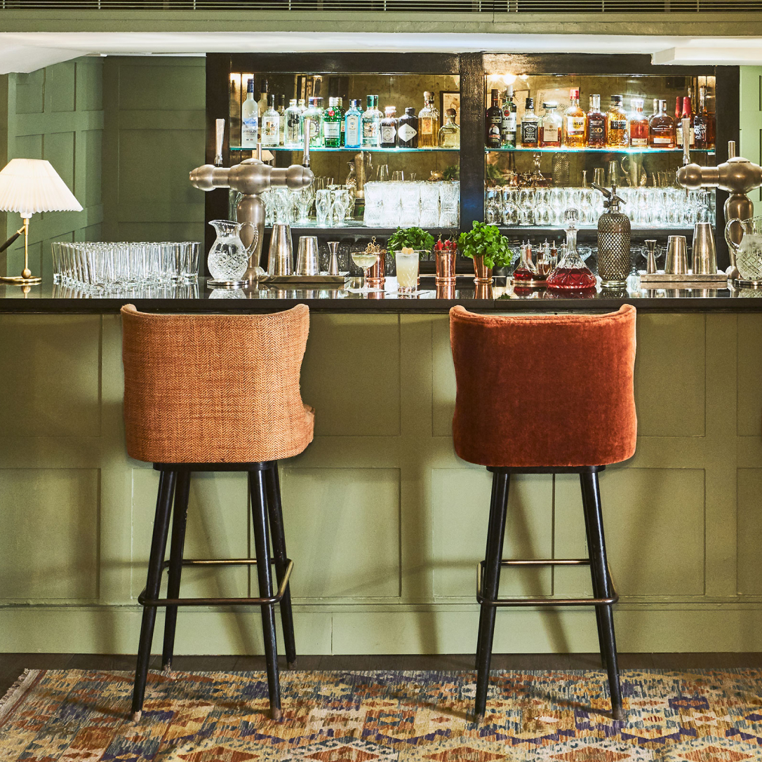 A green bar with two high chairs.