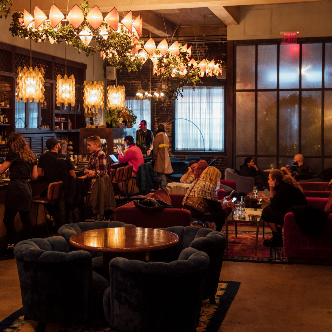 People sat in a relaxed, warmly lit bar interior.