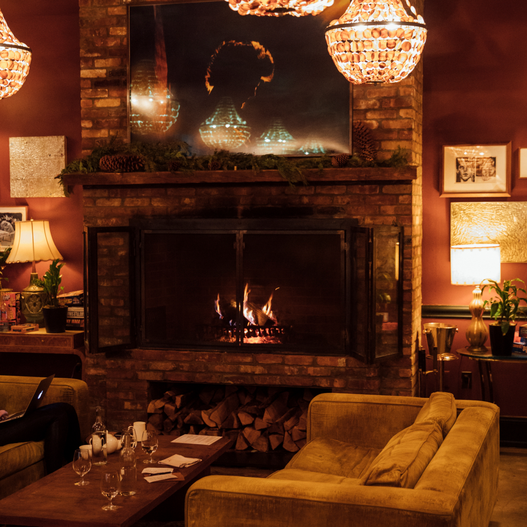 A fire burns in a cosy space full of soft furnishings.