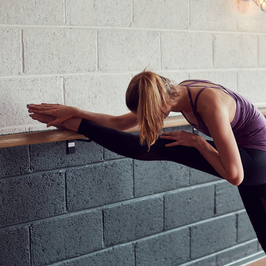 A woman stretches during a barre class.