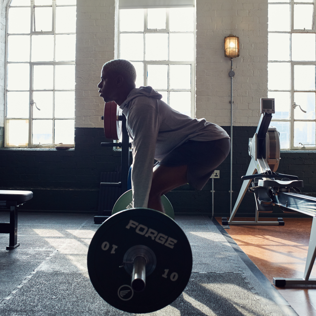 A man lifts a large weight in a gym.