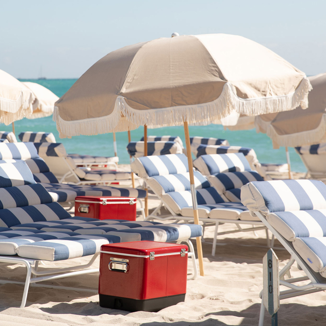 Blue and white striped sun loungers on a beach by the sea with umbrellas and red coolers.