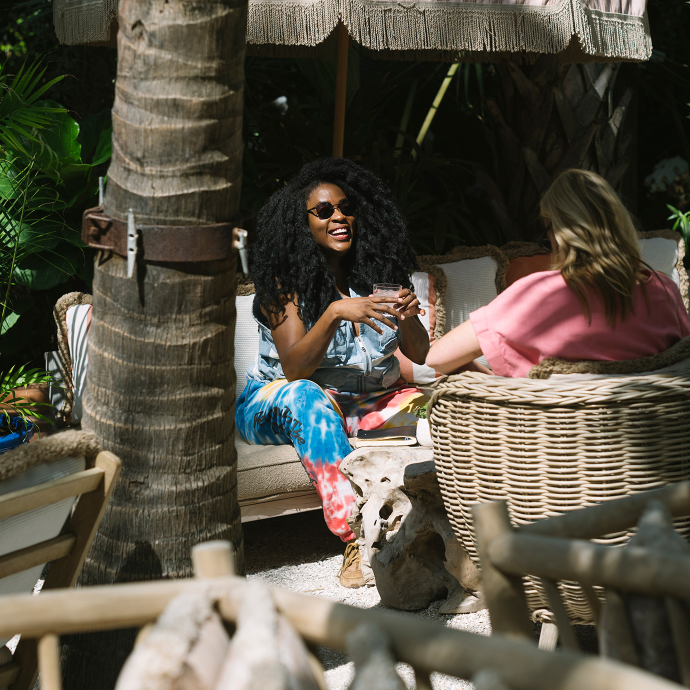 Two women chatting in a tree-shaded bar.