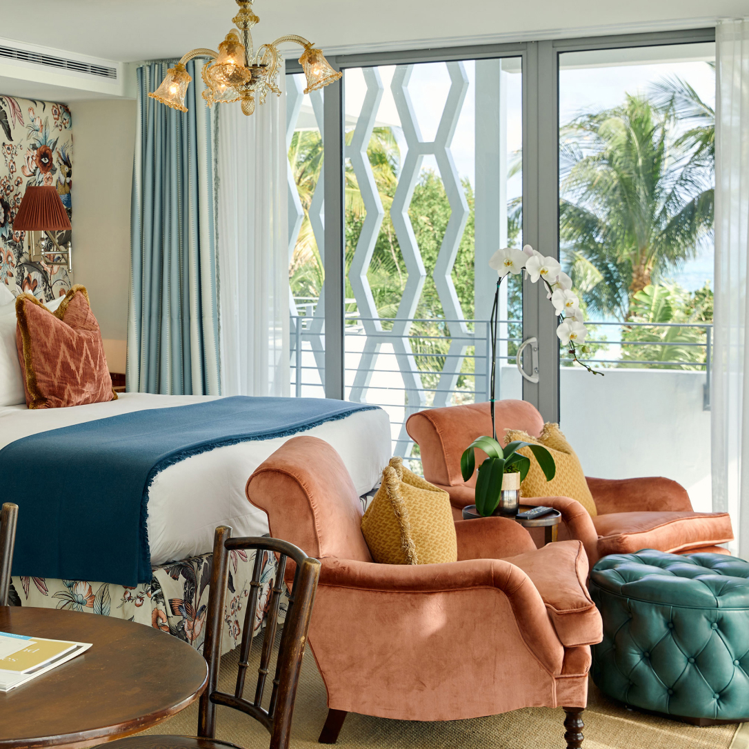 A bed and chairs next to sliding windows looking out onto palm trees.