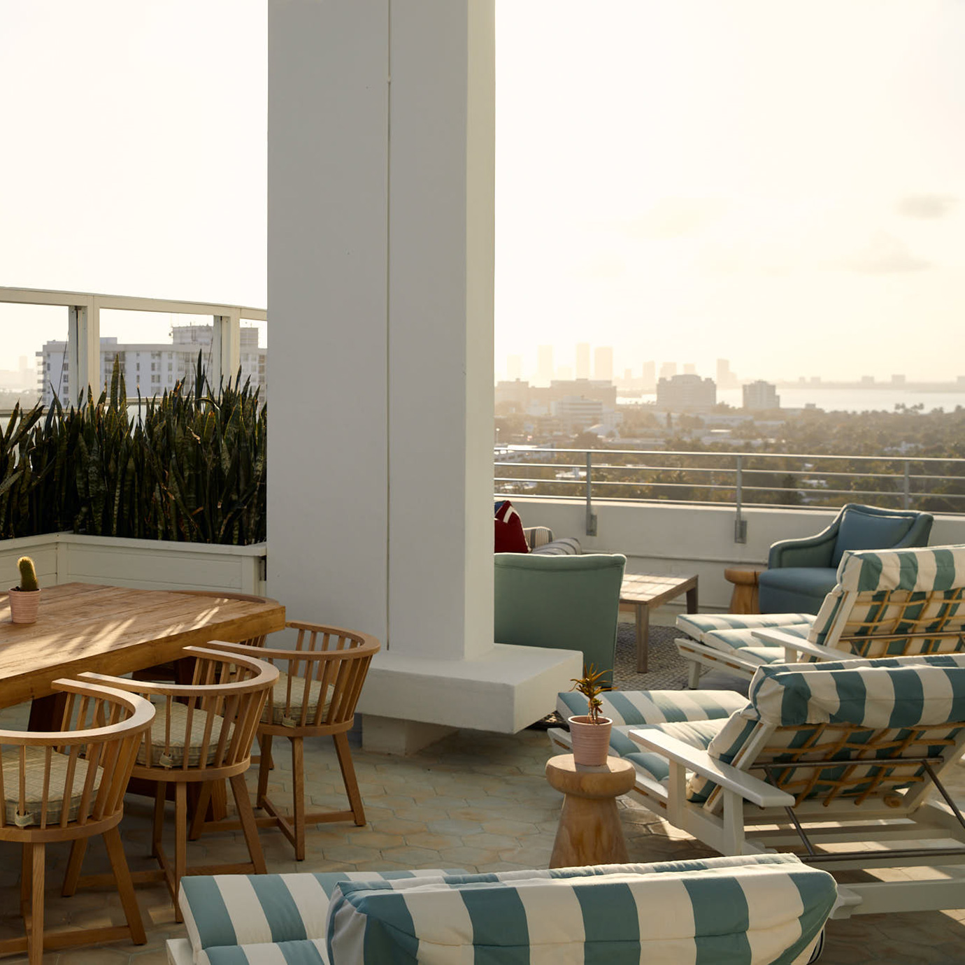 A large roof terrace with dining table and sun loungers.