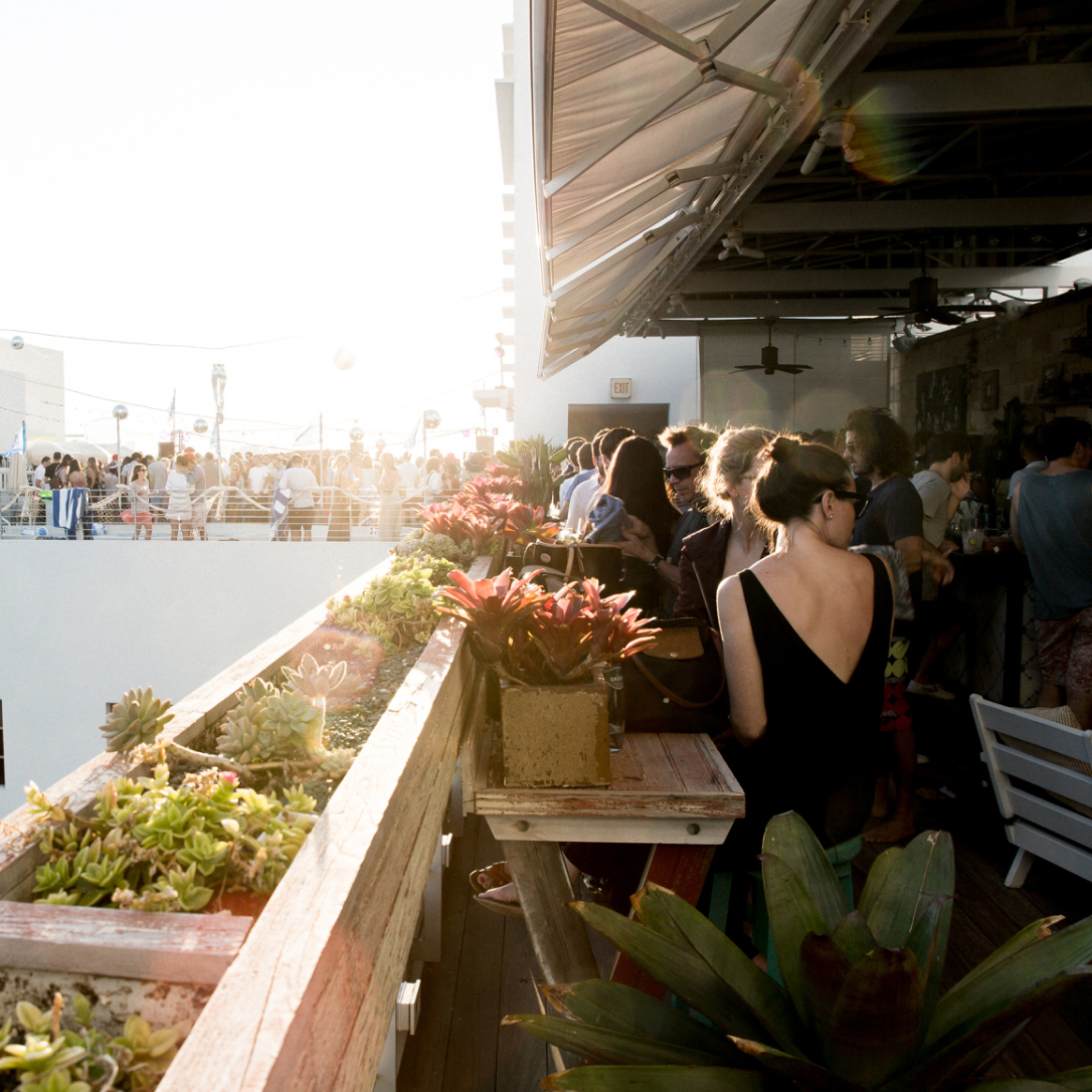 A busy rooftop bar at sunset.