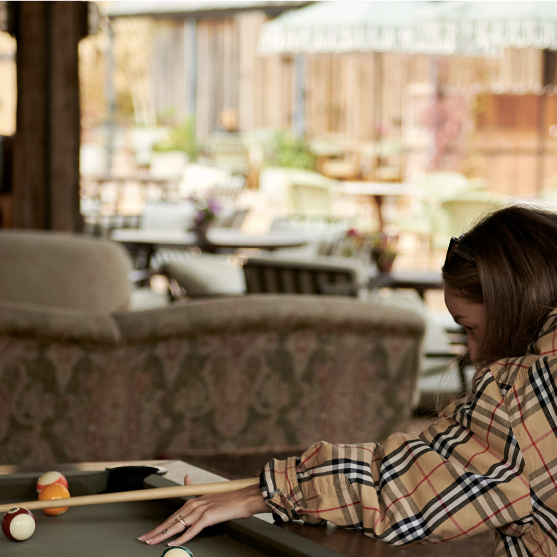 A young woman plays pool in a covered outdoor seating area.