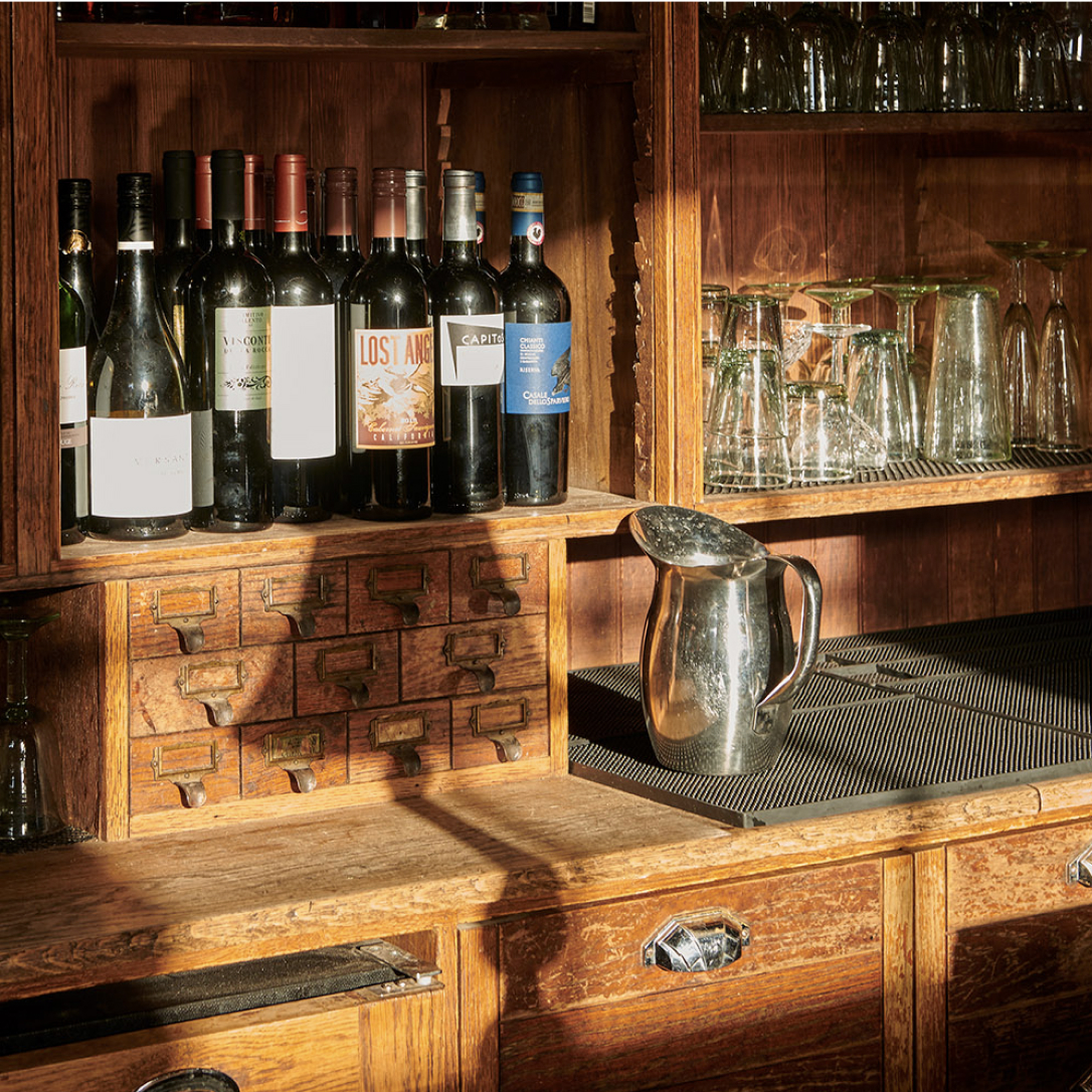 A water pitcher and bottles of wine on vintage wooden shelving behind a bar.