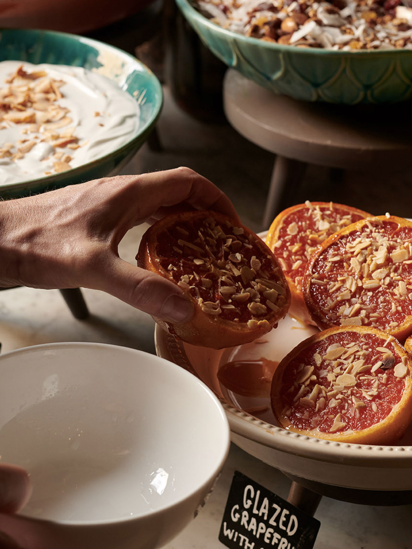 A hand lifts half an orange sprinkled with nuts from a breakfast buffet.