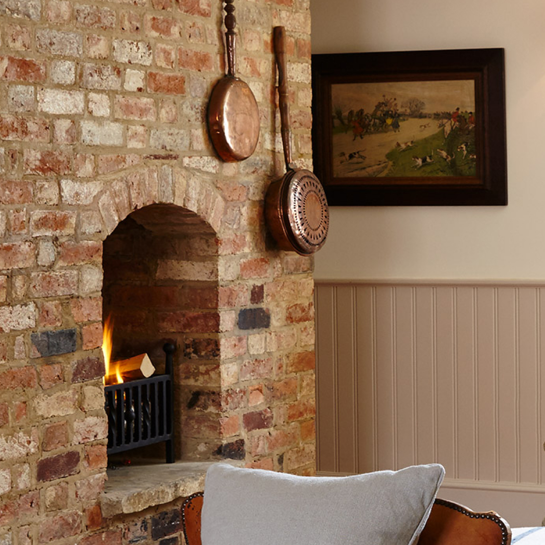 A country-style lounge interior with brick log fire and armchairs.