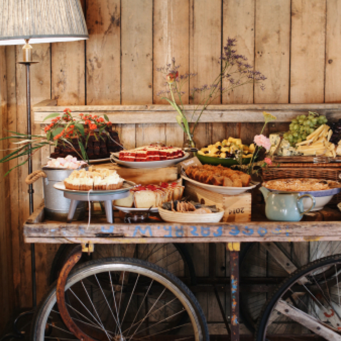 A wooden cart being used as a buffet table with various plates of food displayed on it.