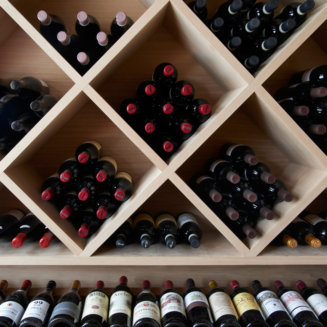 A shelved wine rack with many bottles of wine stored in it.