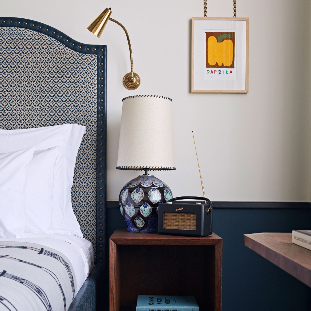 The side of a bed and side table with lamp.