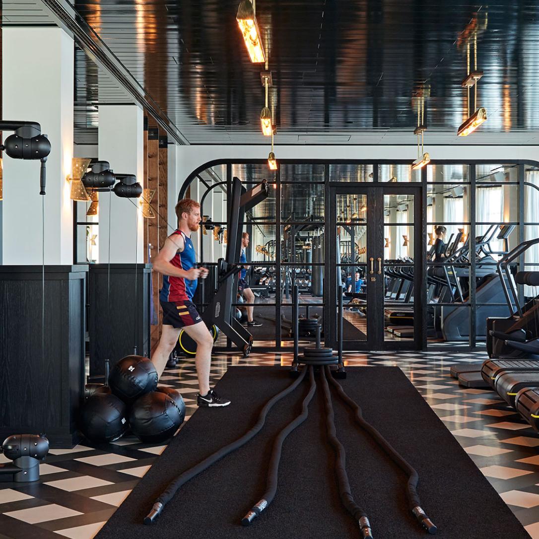 A man using a TRX machine in a gym.