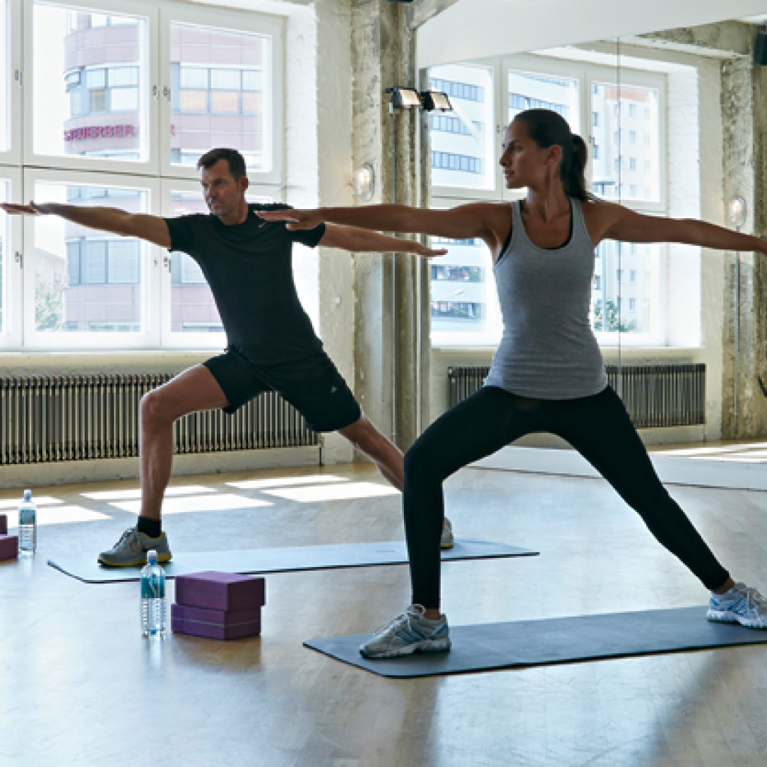 A man and a woman stretching in a yoga class.