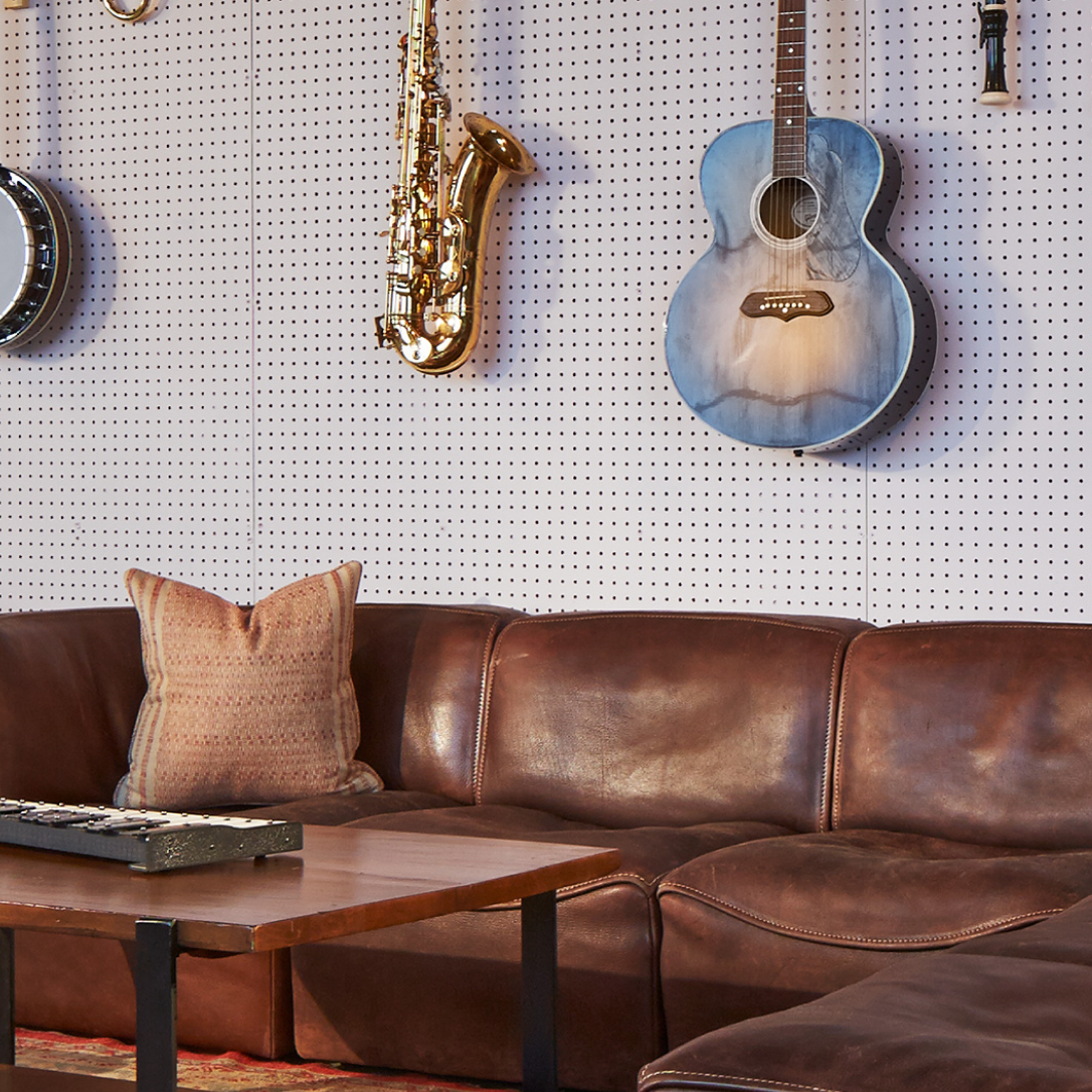 A brown leather sofa with instruments hanging on the wall above it.