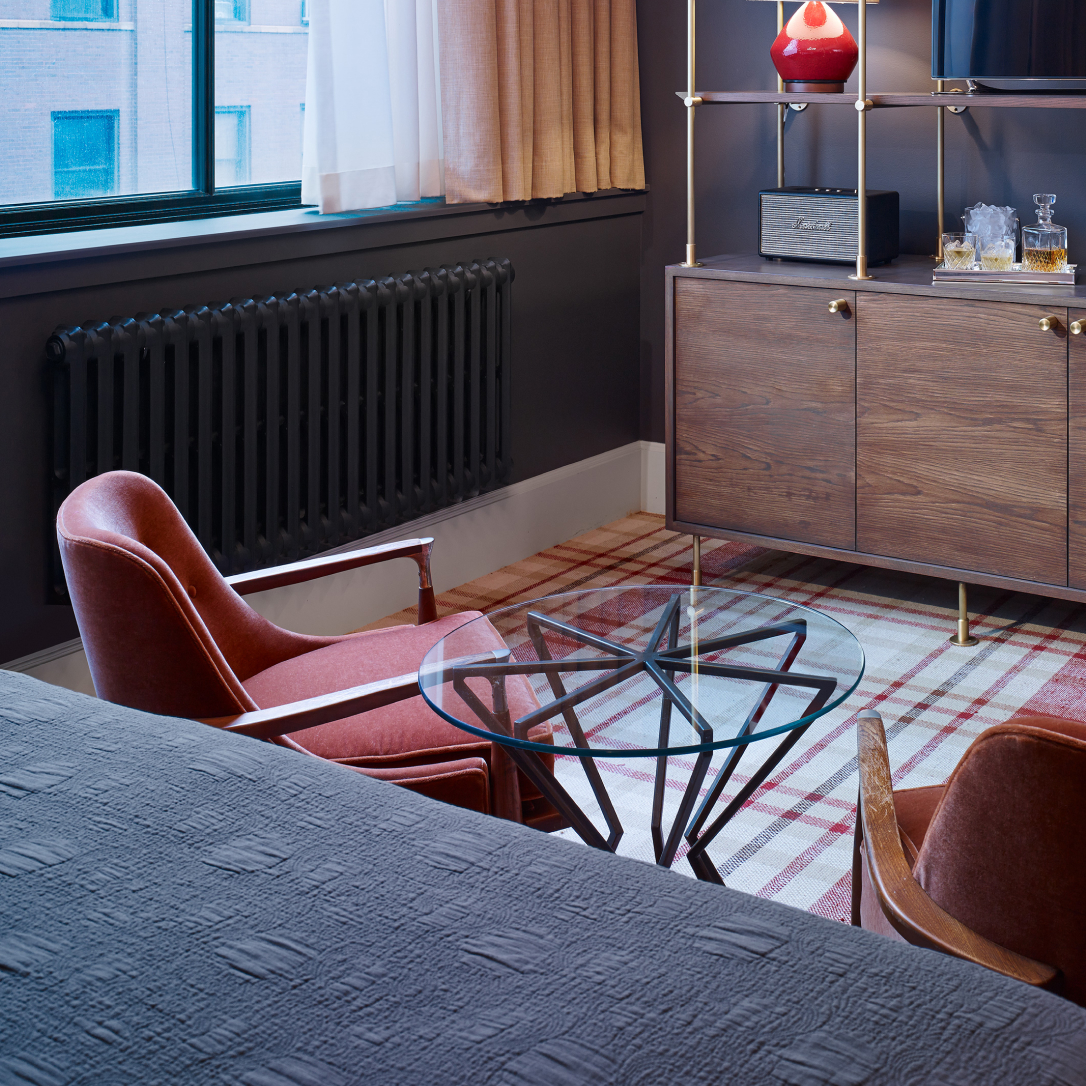Two chairs and a glass coffee table at the end of a bed.