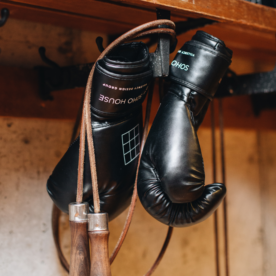 Two black boxing gloves hanging on a hook.