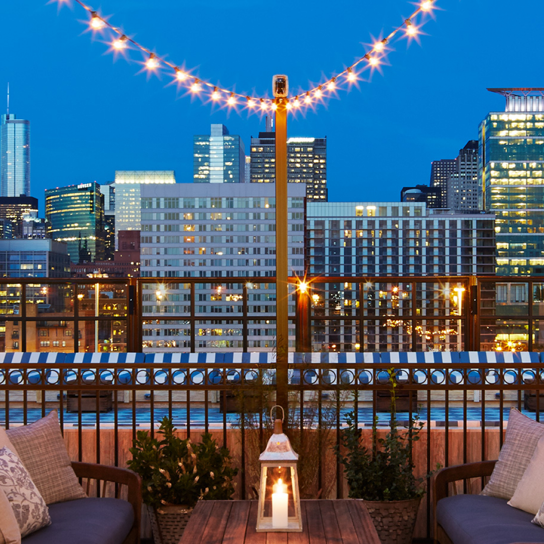 A rooftop seating area with fairy lights above it overlooking a cityscape.