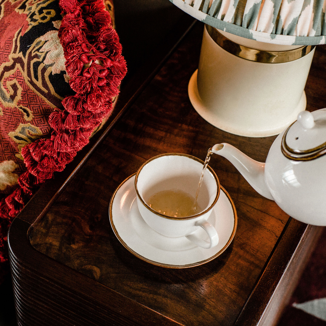 Tea is poured into a cup and saucer from a teapot.