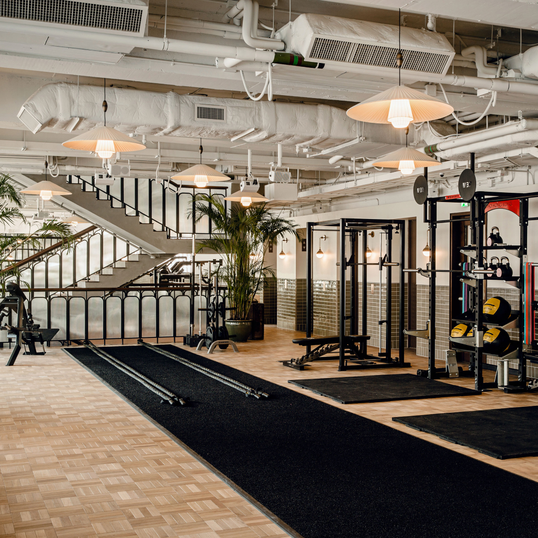 A gym interior with various types of gym equipment in it.