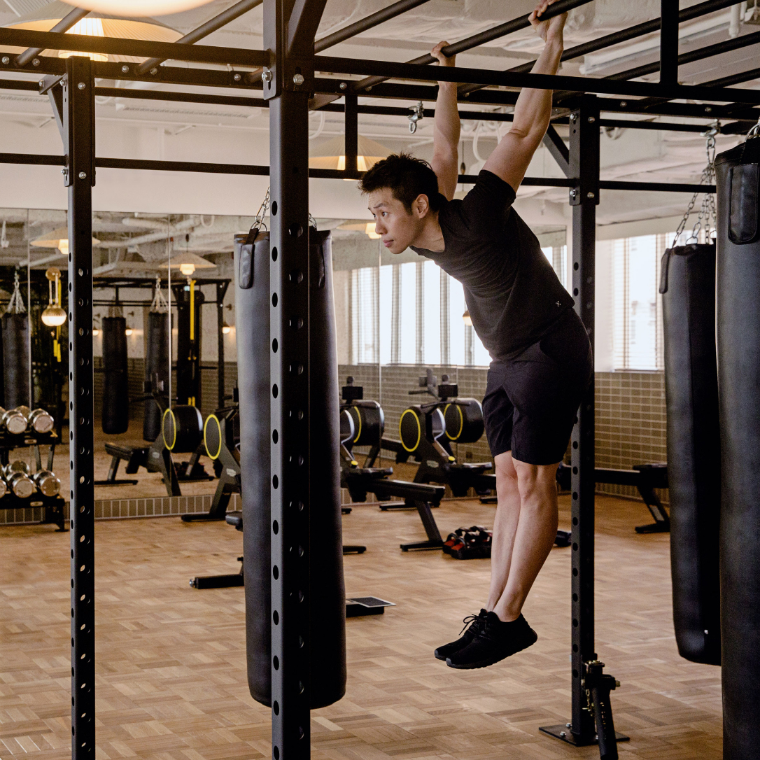 A man lifts himself up on some gym equipment.