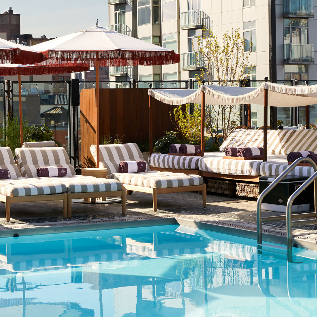 The corner of a rooftop pool with loungers and umbrellas around it.